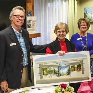 President Tom Andrews presents a giclee of Emily Carr's 'Beloved Trees' to retiring secretary Lynne Landygo, as society treasurer Doreen Zielke looks on.